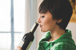 Portrait of young handsome caucasian brown hair woman smelling a bottle of red wine like a sommelier, eyes closed - beverage, happy hour concept