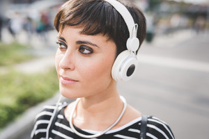 Portrait of young handsome caucasian brown straight hair woman listening music with headphones, overlooking right, pensive - music, relax, thoughtful concept