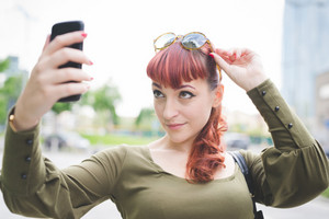 Portrait of young handsome caucasian redhead woman using smartphone, taking up her sunglasses, taking a selfie, wearing a green shirt - vanity, social network concept