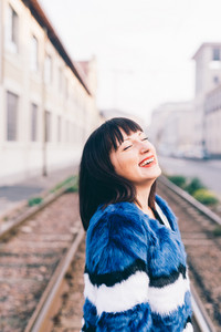 Portrait of young handsome eastern woman outdoor in the city having fun laughing - happiness, carefree, serene concept