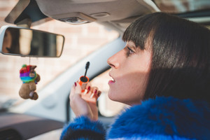 Portrait of young handsome eastern woman putting on make up in her car, using rear-view window - vanity, make up, beauty concept