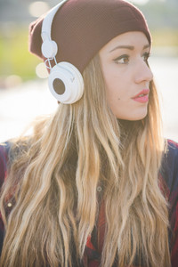 Portrait of young handsome long straight hair woman listening music with headphones in backlight, overlooking, pensive - music, technology, thinking future concept