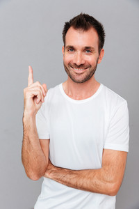 Portrait of young handsome smiling carismatic man having an idea and pointing finger up isolated on a grey background