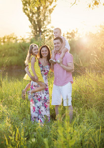 Portrait of young happy family in sunny meadow