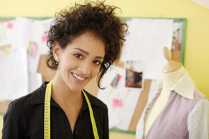 Portrait of young hispanic female dressmaker with mannequin in background. Horizontal shape, head and shoulders, copy space