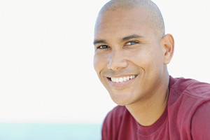 portrait of young hispanic guy with shaved head looking at camera near the sea. Horizontal shape, head and shoulders, copy space