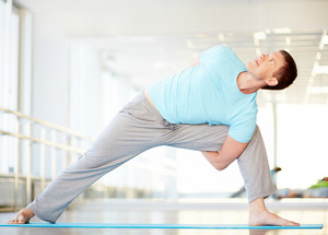 Portrait of young man doing stretching exercise in gym