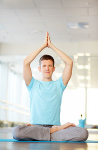 Portrait of young man doing yoga exercise in gym