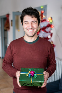 Portrait of young man holding christmas present - celebration, christmas time, gift concept