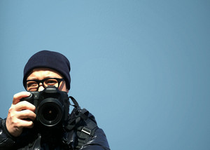 Portrait of young man photographer with camera. paparazzi