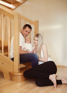 Portrait of young parents having fun at home with their newborn boy