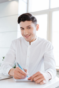 Portrait of young smiling man dressed in white shirt writing notes in notebook. Coworking. Looking at camera.