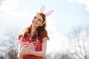 Portrait of young smiling red head woman wearing bunny ears and holding easter basket with painted eggs outdoors