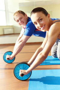 Portrait of young sporty couple doing exercise on floor