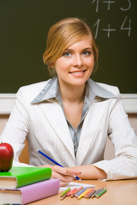 Portrait of young teacher checking up copybook with books near by and looking at camera with smile