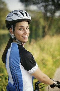 portrait of young woman training on mountain bike and smiling at camera and looking over the shoulders