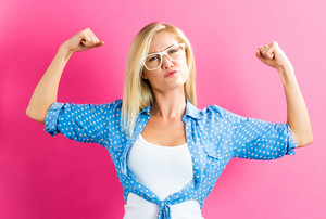 Powerful young blonde woman on a pink background