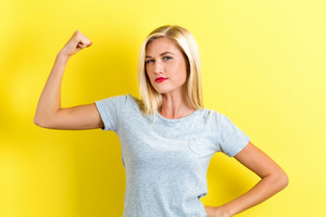 Powerful young woman on a yellow background