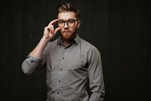 Pportrait of a stylish bearded man in eyeglasses and shirt looking at camera isolated on the black wooden background
