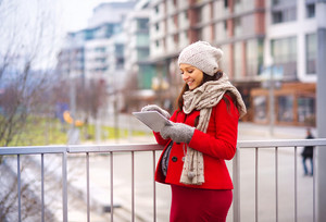 Pregnant woman in knitted clothes holding digital tablet, outside in winter weather