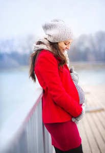 Pregnant woman in knitted clothes holding her belly, outside in winter weather