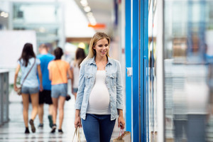 Pregnant woman in white t-shirt and denim shirt in shopping center, walking.