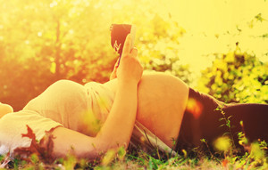 Pregnant woman outside holding baby shoes to her belly