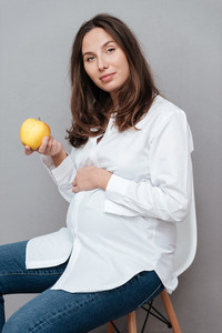 Pregnant woman with apple. sitting on chair. looking at camera