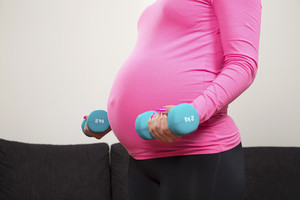 Pregnant young woman exercising with training weights indoor