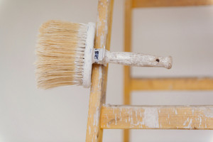 Preparing to paint the wall. Detail of paintbrush on ladder.
