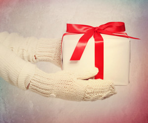 Present box with big red bow in womans hands with white warm gloves