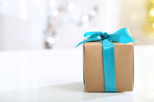 Present box with teal bow in a bright room
