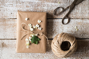 Present wrapped in brown paper decorated by lilac flower. Scissors and ball of yarn laid on table. Studio shot on white wooden background.