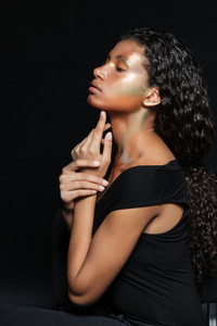Pretty african woman in profile. in studio. isolated black background