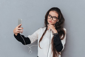 Pretty Asian woman in glasses and headphones making selfie. Isolated gray background