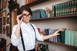 Pretty Authoress in glasses and white shirt selecting the book on bookshelf and looking at camera