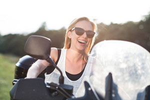 Pretty blond woman enjoying a quad bike ride in countryside. Girl driving off-road with ATV.
