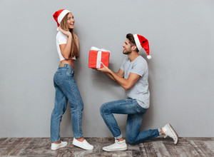 Pretty Couple christmas gift. girl surprised. gray background