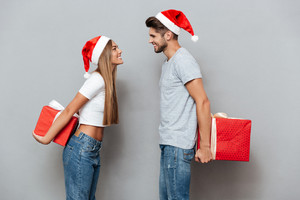 Pretty couple with christmas surprise. Smiling. gray background. in santa's hats