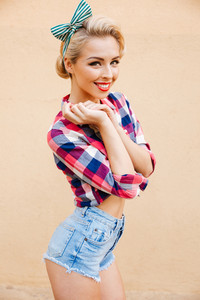 Pretty cute pinup girl in plaid shirt standing and smiling over pink background