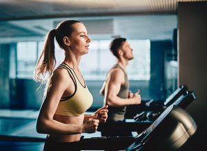 Pretty girl running on treadmill on background of guy