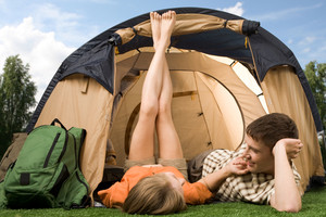Pretty girl touching boyfriend while lying on grass near tent during summer vacations