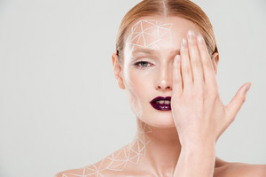 Pretty model with body art closes her eye. Close up. Beautiful make up. Isolated gray background