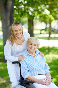 Pretty nurse and senior patient in a wheelchair looking at camera in park