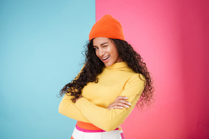 Pretty playful african young woman in hat standing with arms crossed and winking over colorful background