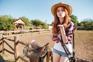 Pretty redhead cowgirl in straw hat sending air kiss while sitting on the fence