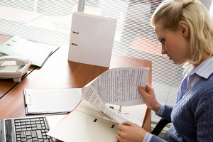 Pretty secretary working with papers in office