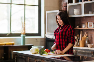 Pretty Woman in red shirt cooking in kitchen. Side view