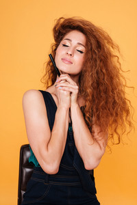 Pretty woman with red curly hair holding eyeliner with eyes closed isolated on orange