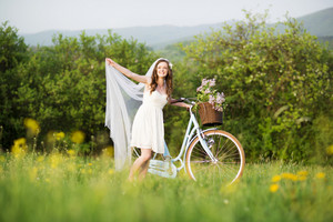 Pretty young bride riding retro bike in green meadow